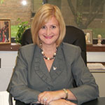 Principal Lisa Hankinson smiling with blonde chin-length hair wearing a green blazer sitting at her desk