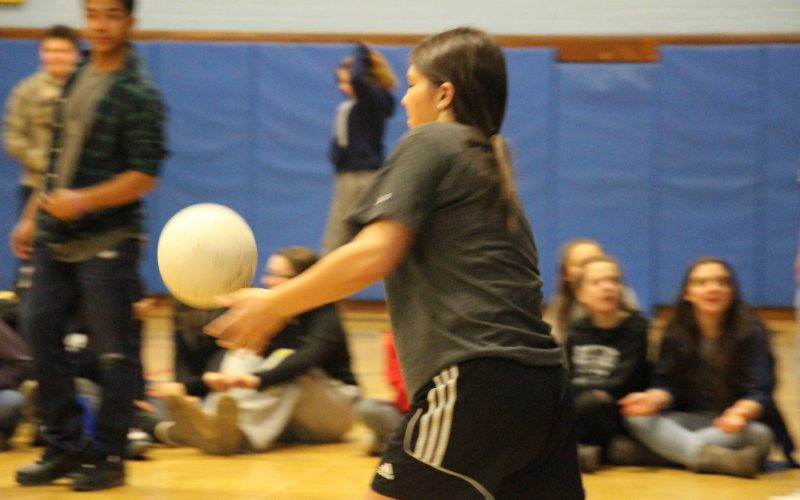 A teacher serves during the volleyball game with students watching in background