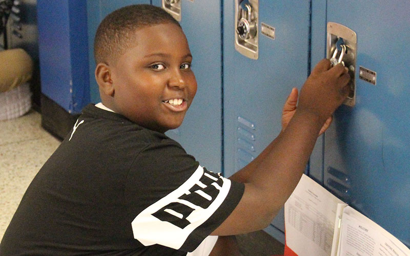 Circleville Middle School student opening his locker and smiling
