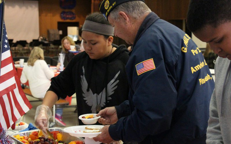 A middle school student serves breakfast to a veteran at Circleville Middle School