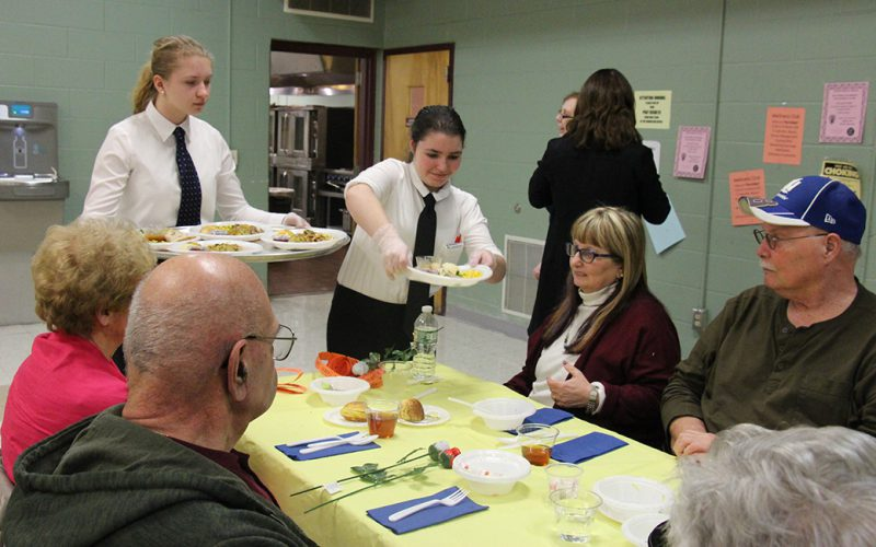Two high school students serve dinner to senior citizens at Pine Bush High School