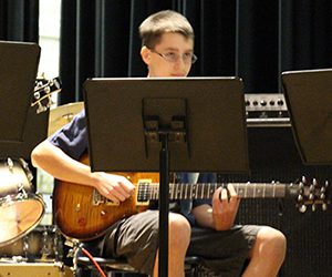 Student with glasses sitting and playing an electric guitar