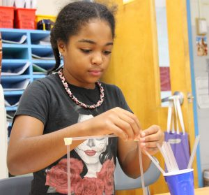 Student in black shirt and pink and black necklace builds a structure out of plastic straws