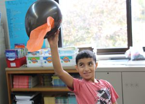 Boy in red t shirt holding up his black balloon with a piece of crepe paper attached to it