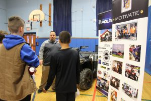 .A man wearing a quarter zip gray pullover jacket stands in front of a four-wheeler and talks to several students.