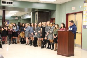 Approximately 20 middle and high school girls stand in a line next to a podium where their coach, a man with a blue hoodie talks into a microphone