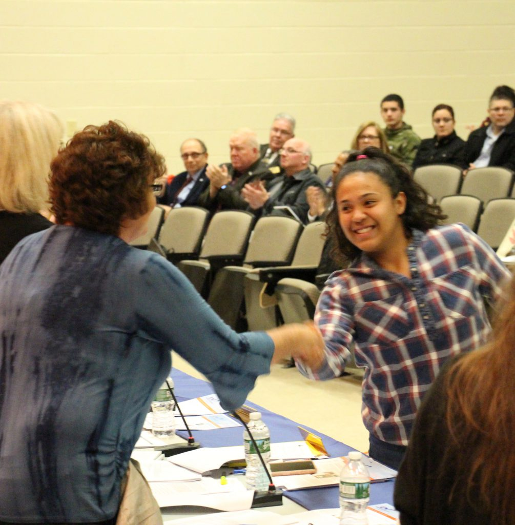 A high school girl with long dark hair dressed in a plaid shirt shakes hands with a board member in a blue shirt