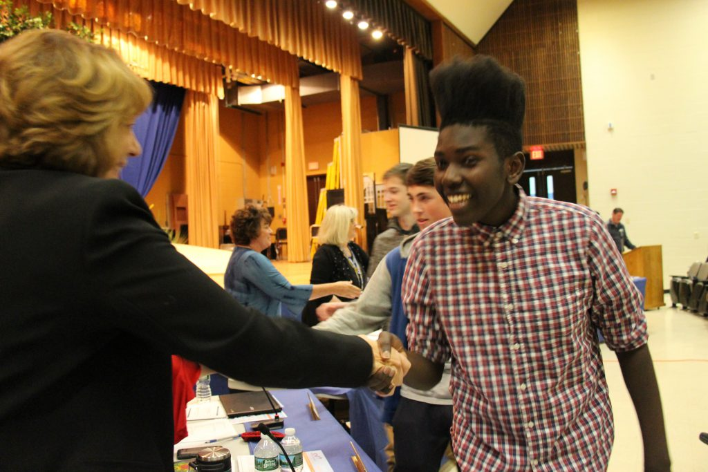 A male high school athlete smiles while shaking hands with the assistant superintendent.