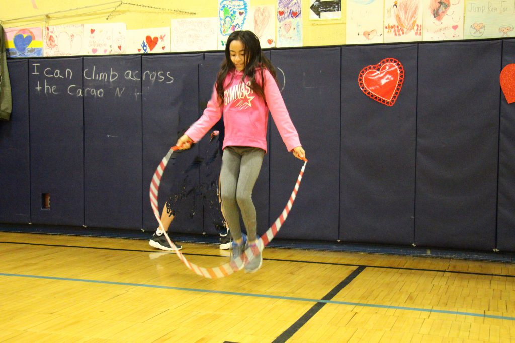 Elementary student dressed in pink shirt jumps rope in the gym.