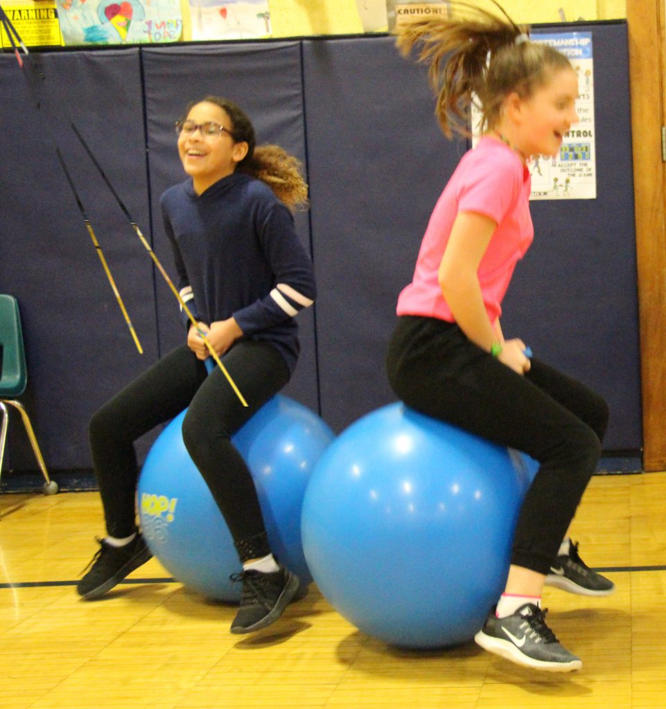 Two fifth-grade girls bounce on bright blue, large rubber bouncing balls.