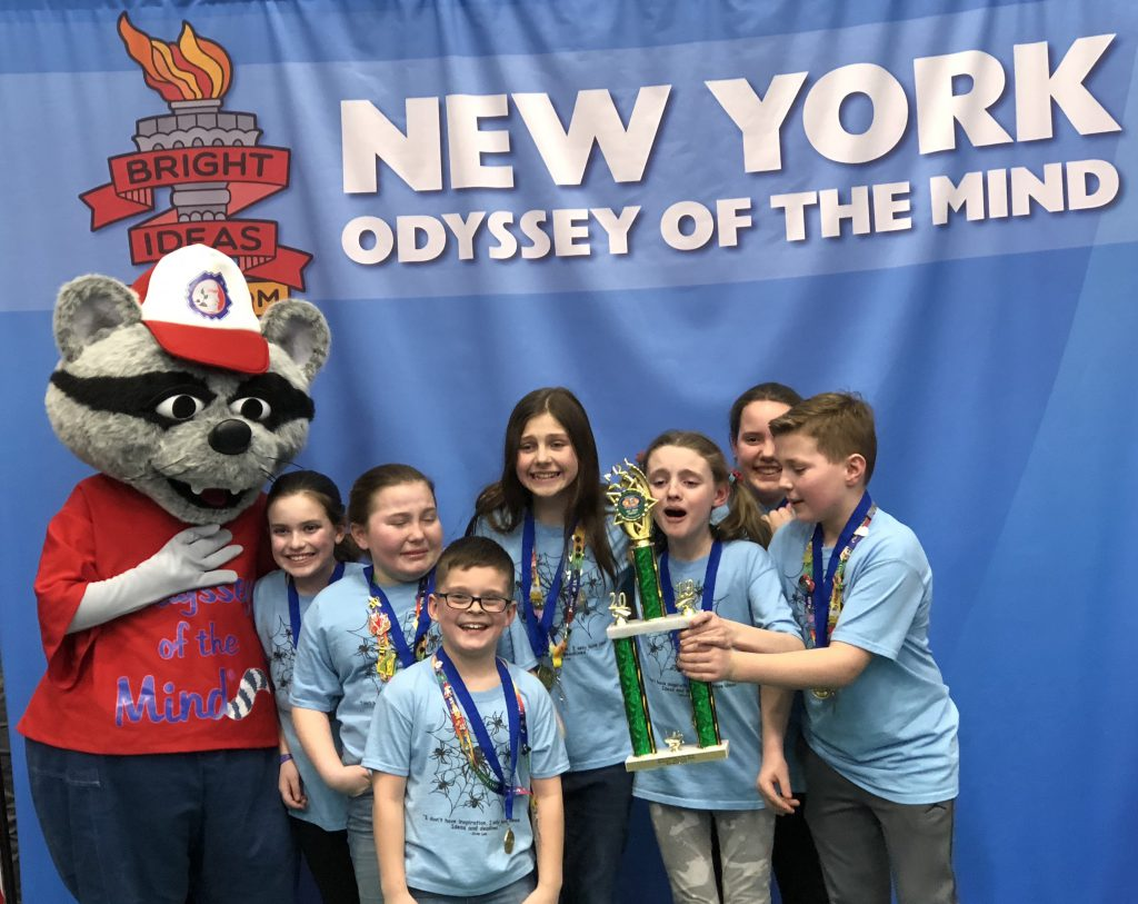 Seven elementary students have medals around their necks and hold their trophy with the Odyssey of the Mond mascot, a large raccoon character dressed in red.