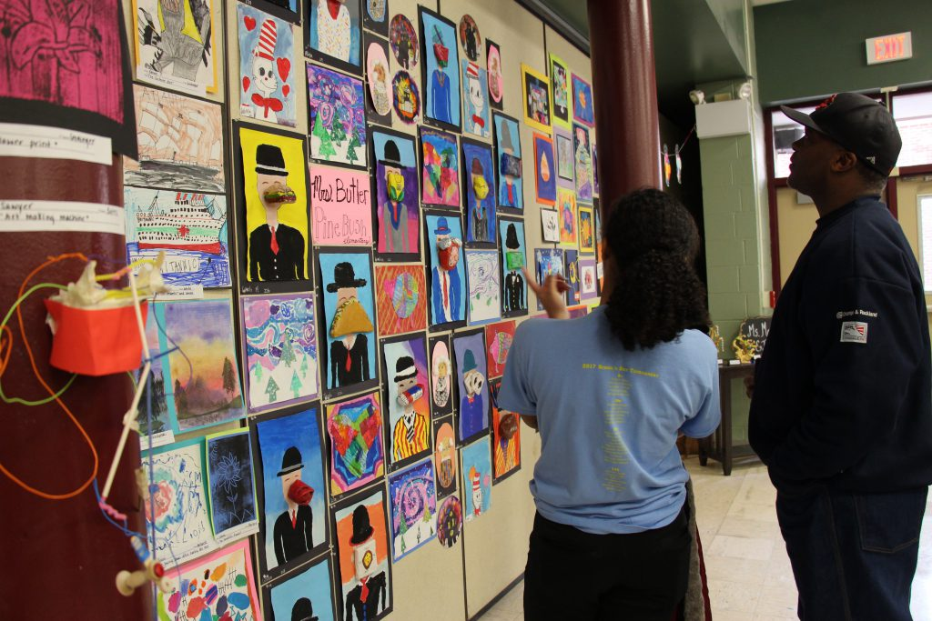 A parent and a student look at a wall of art