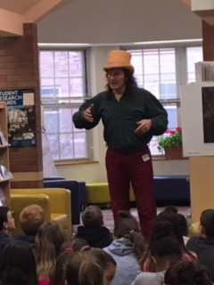 Students sitting on the floor listening as a may wearing a tan top hat acts out a story
