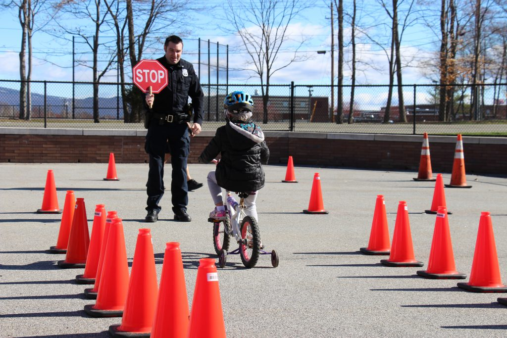 Kindergarten student on a bike with training wheels riding between cones with a police officer in front holding a stop sign.