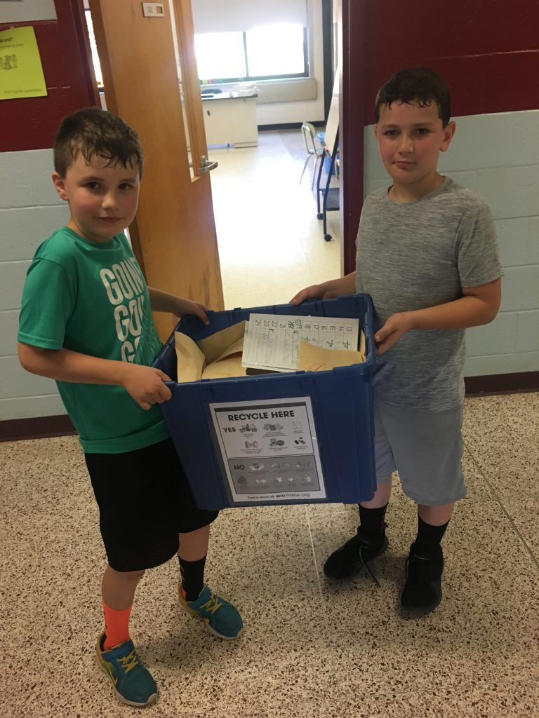Two boys carry a blue recycle bin.