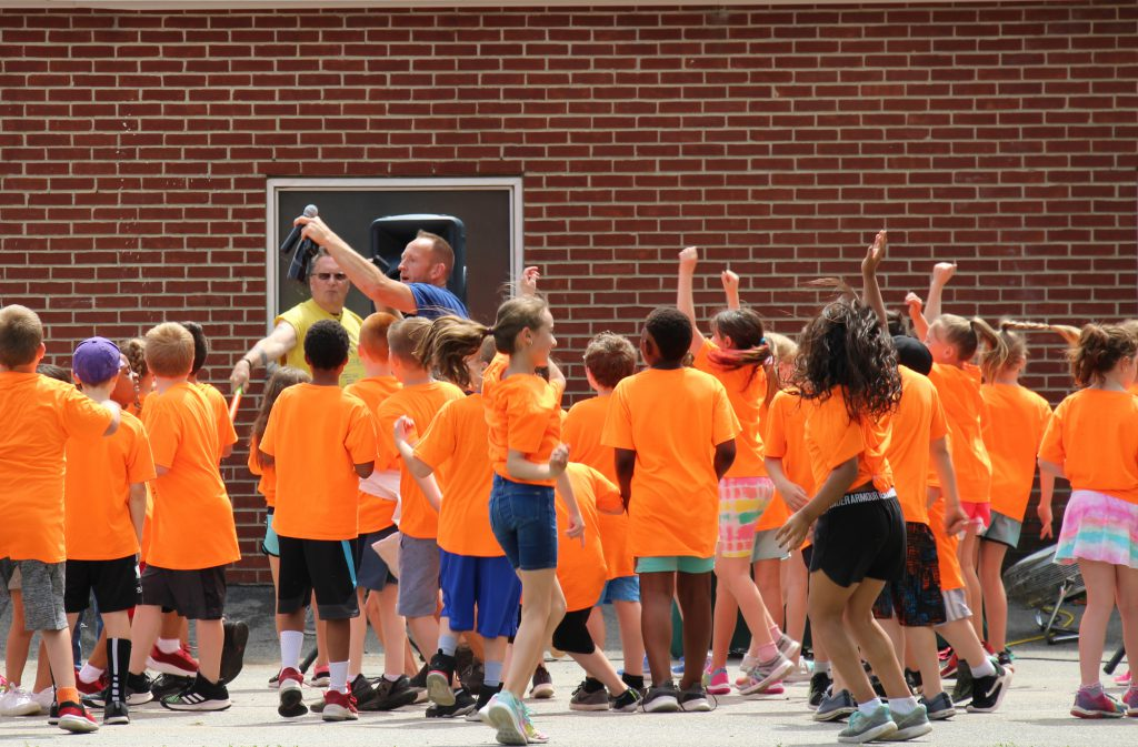 A large group of elementary students, all wearing orange t-shirts, dancing