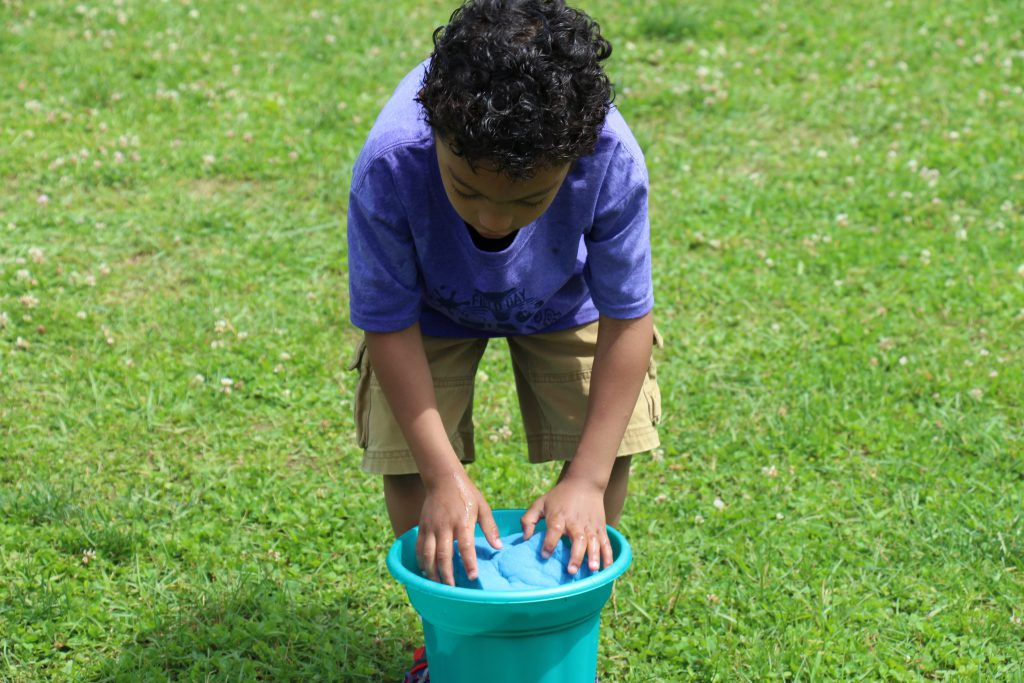 Little boy in purple shirt and tan shorts leaning over a bucket of water with a sponge in his hands.
