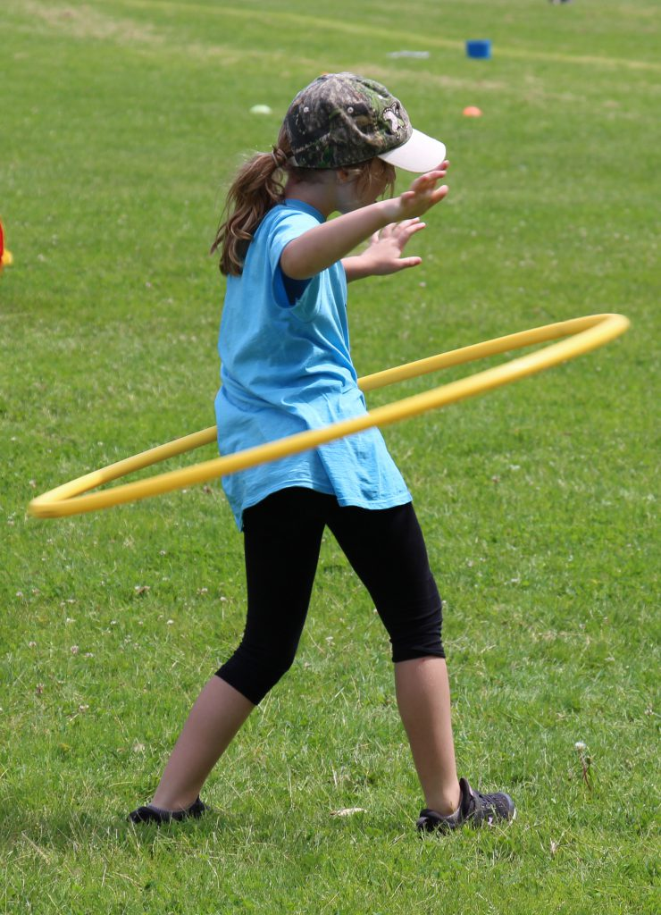 Girl in a light blue t-shirt and baseball cap does the hula hoop