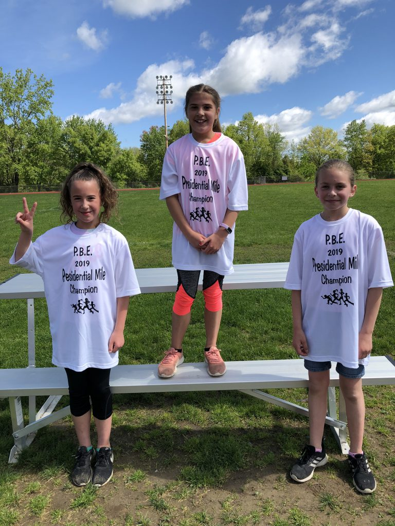 Three fourth-grade girls wearing white presidential mile t shirts. Winner in center stands higher. The girl on the left is holding up her index figure to show they are number 1.