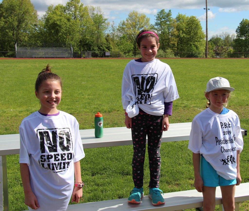 Three third-grade girls dressed in white t-shirts noting the presidential mile. First place winner in center standing higher than the others