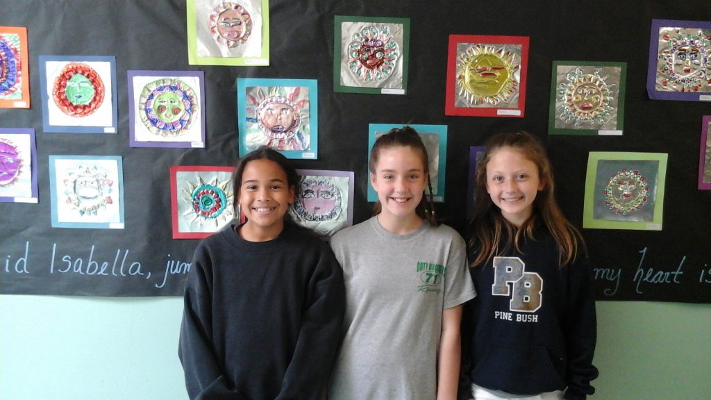 Three older elementary school girls stand in front of a wall of art.
