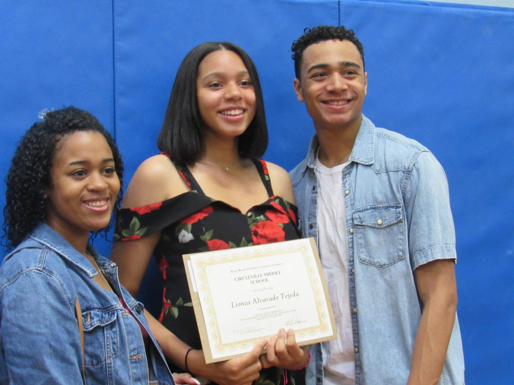 A young woman wearing a black and red dress holds her certificate while flanked by a man and woman.