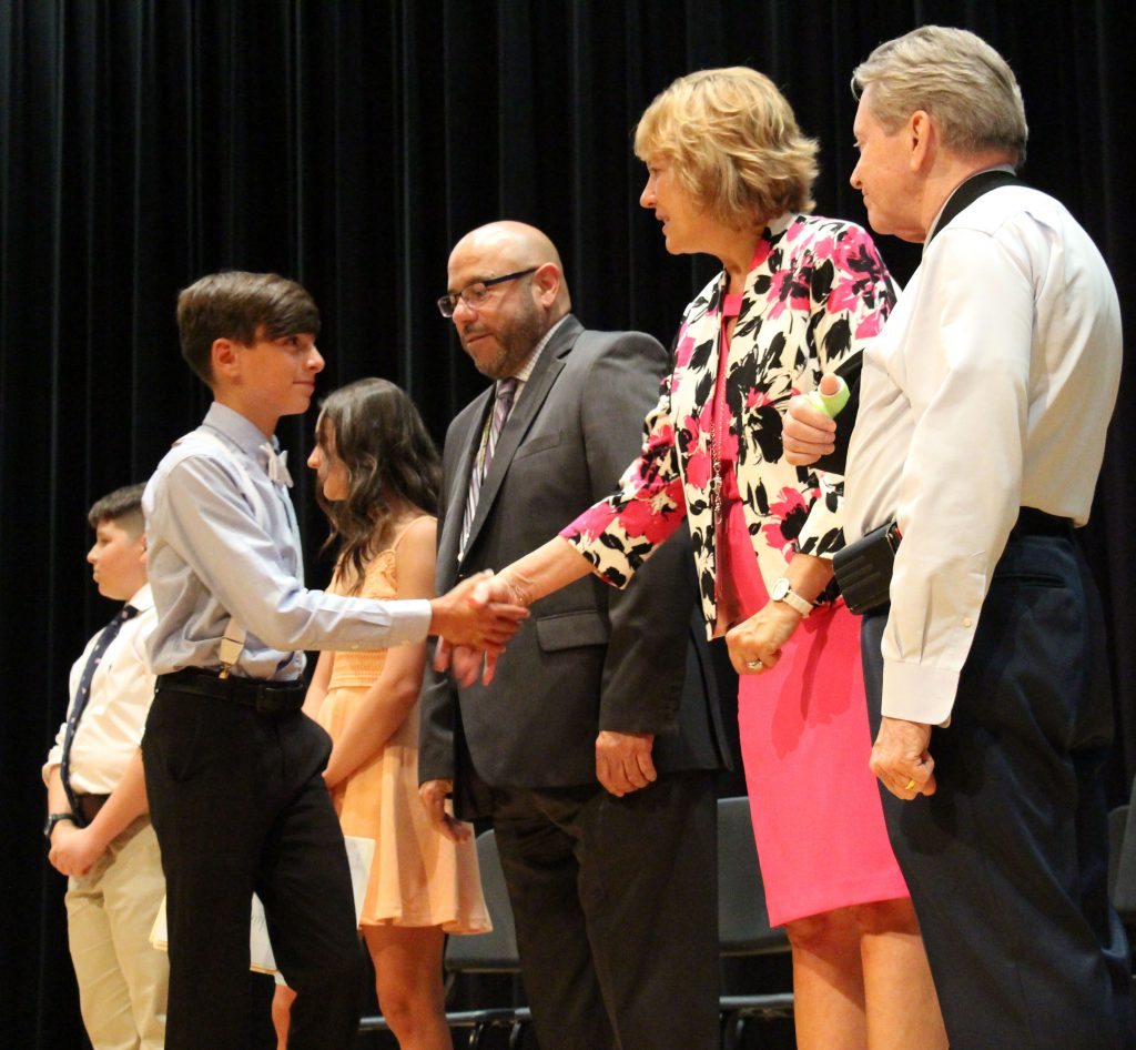 A young man in a shirt and tie shakes hands with a woman in a pink dress as other administrators look on