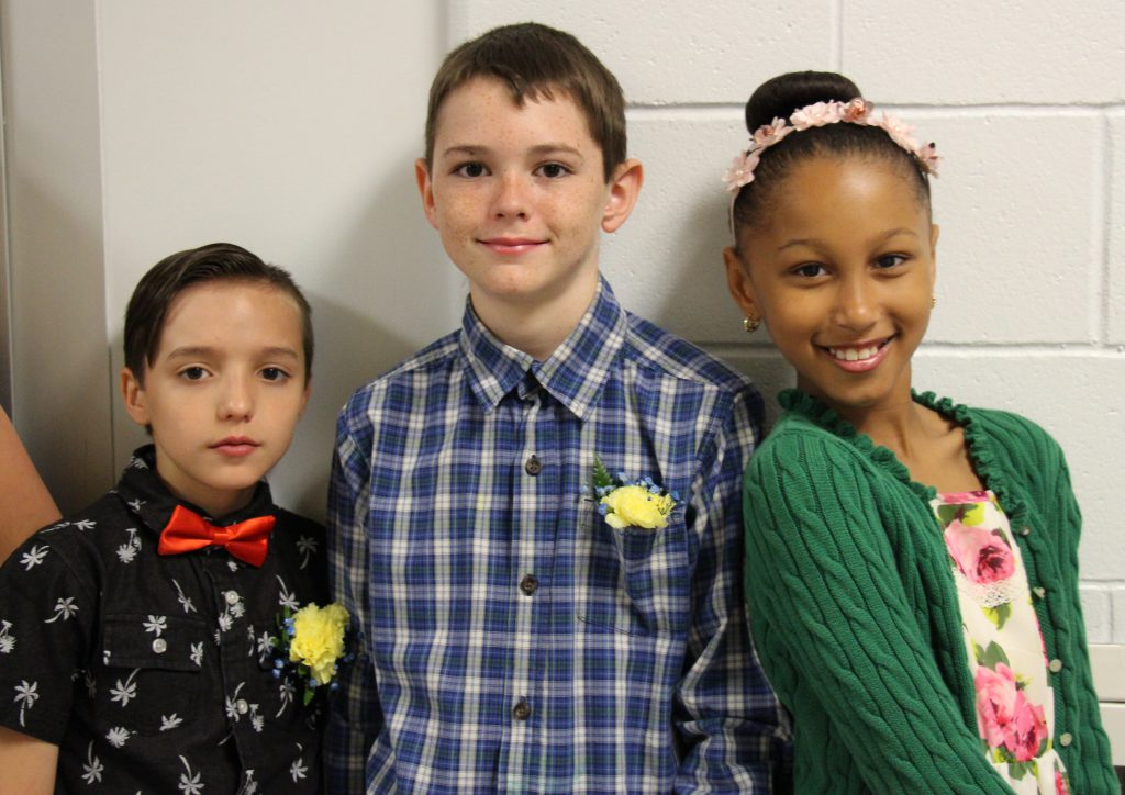 Three fifth-grade students stand against a wall, On left is a boy in a black shirt and red bow tie, boy in center is wearing a plaid shirt, girl on right has her hair in a bun and is wearing a green sweater. They're smiling and wearing flowers pinned to their shirts.