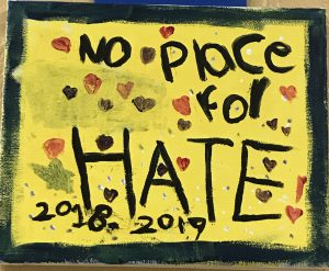 A handpainted sign saying No Place For Hate 2018-2019 with hearts and stars