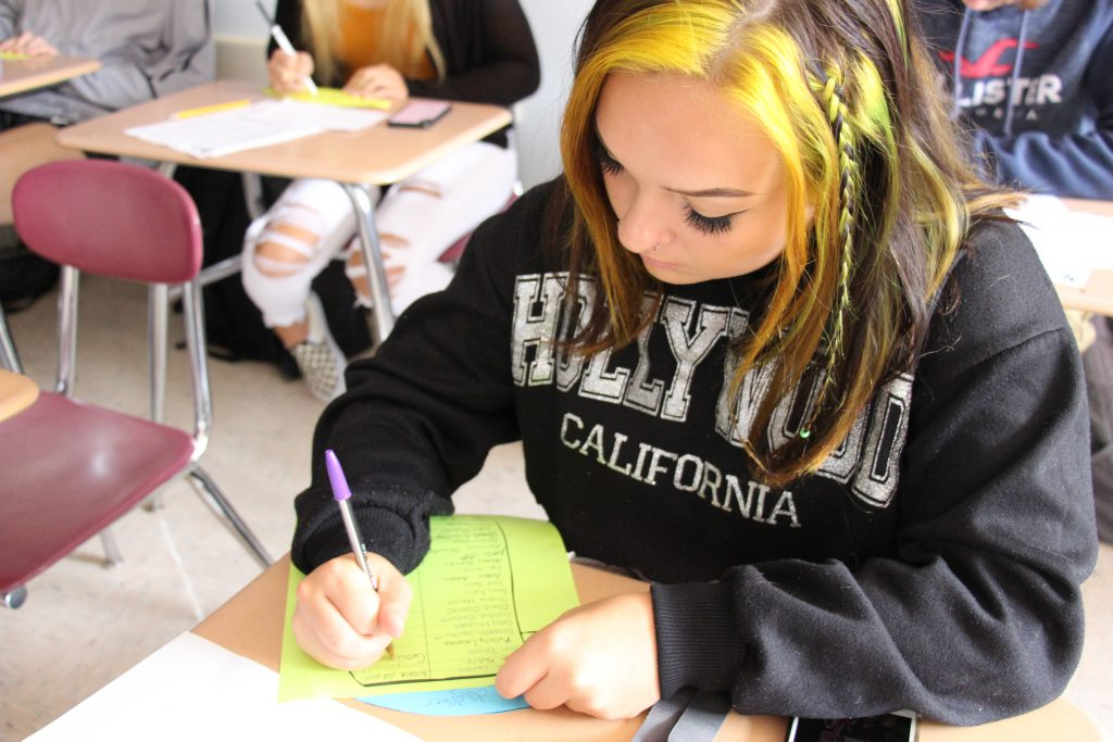 A high school senior girl wearing a Hollywood California sweatshirt sits at a desk and writes on a piece of paper