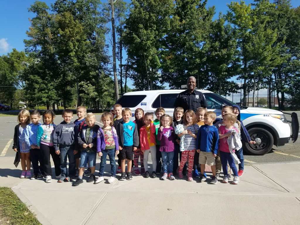 A police officer stands in front of his car with 20 kindergarten students