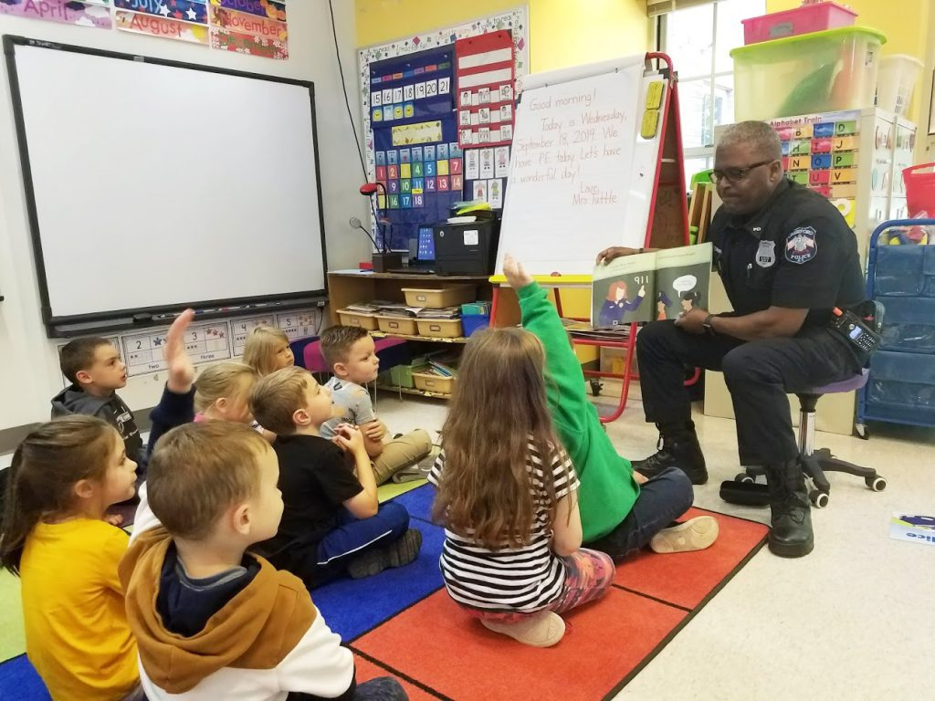 A police officer is sitting in front of the class with a book opened toward the students who are facing him, sitting on a rug. Some students have their hands up