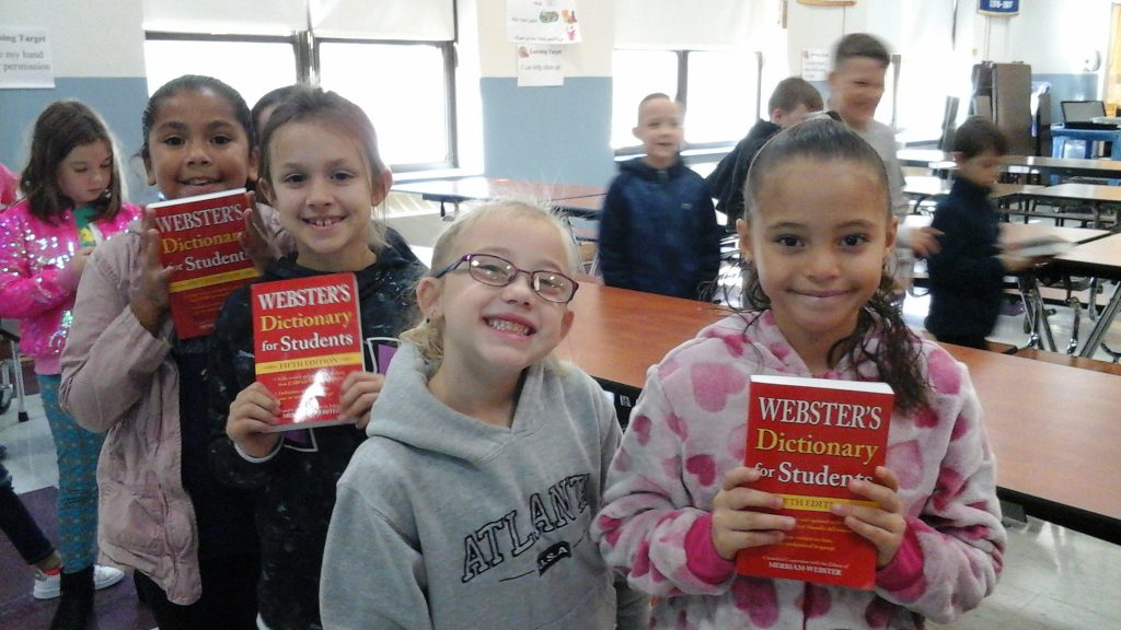 A group of five third-grade boys and girls smile as they hold up their new red dictionaries