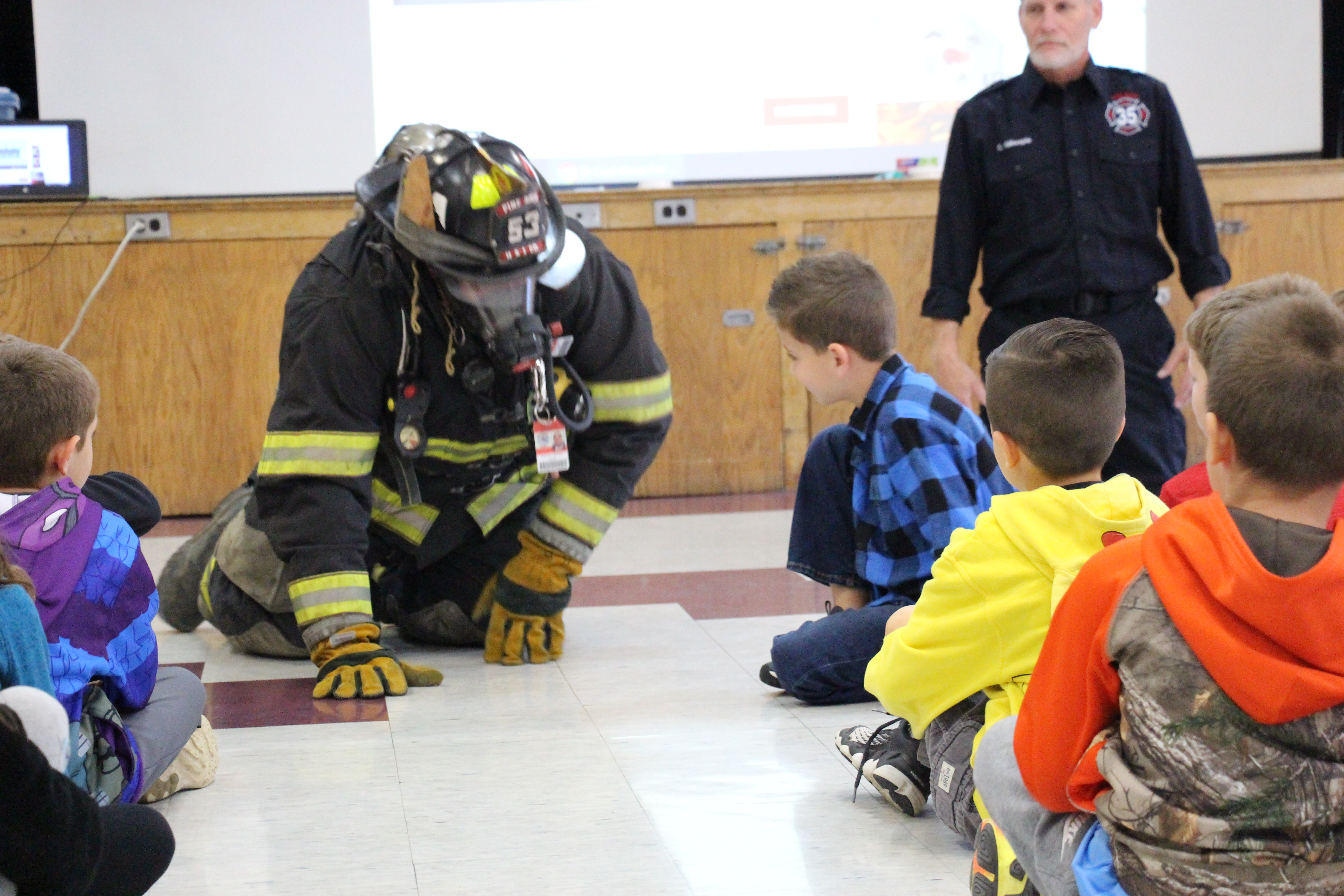 A man in full firefighter gear is on his hands and knees about to crawl through a group of elementary school students.