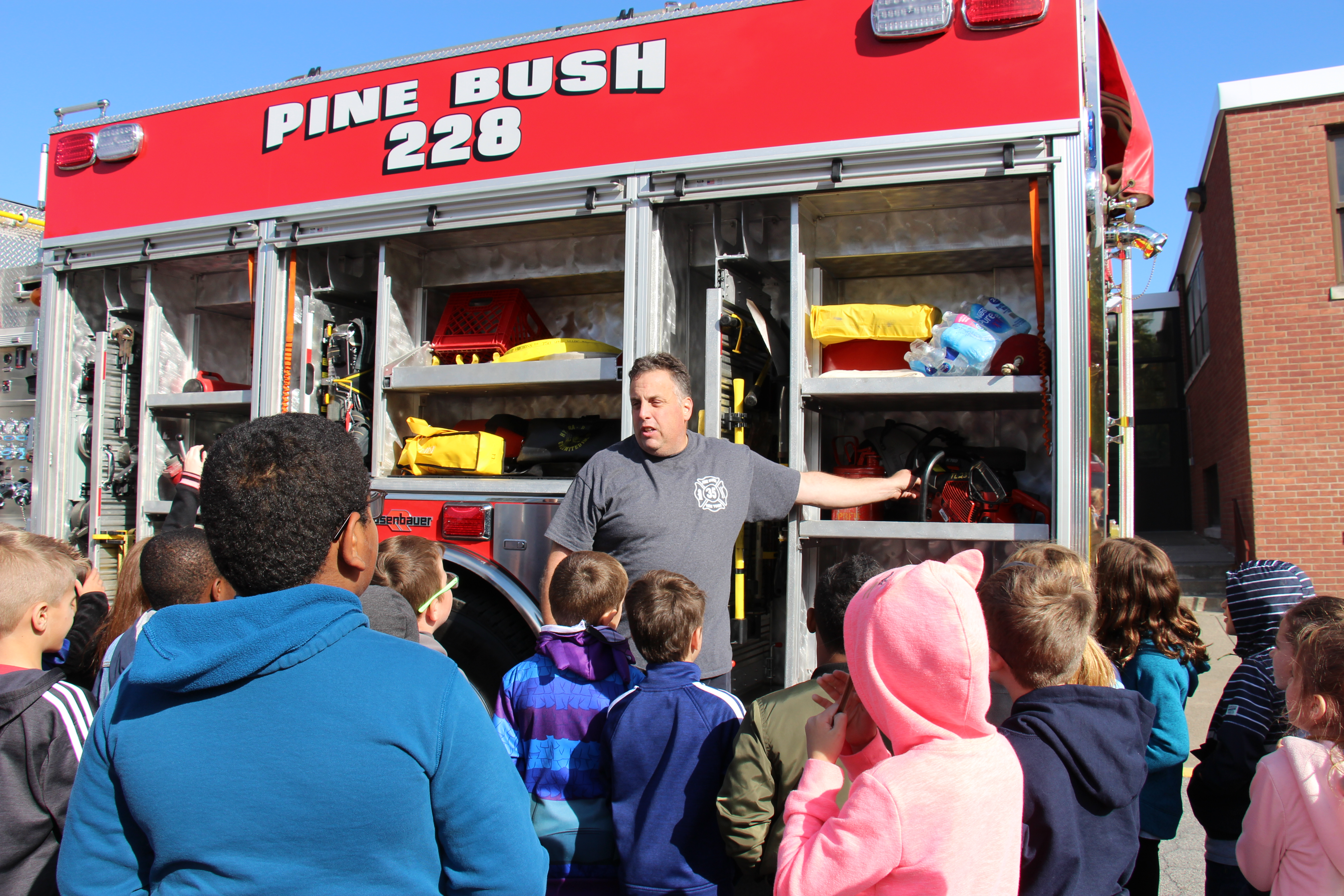 A large group of elementary students listen as a man stands in front of a fire engine pointing out all of its equipment during fire safety week.