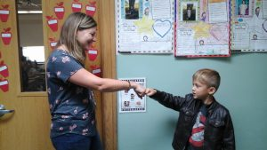 A female teacher standing in a doorway fist bumps a young male student