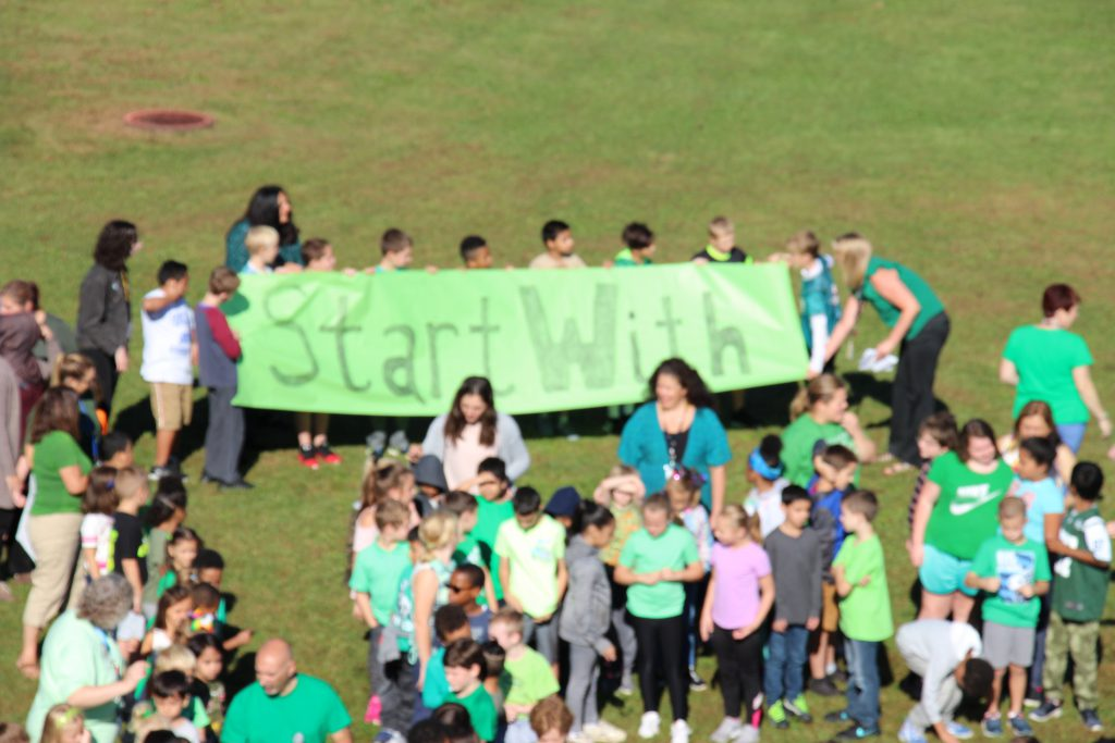 """Students hold a green sign that says """"Start With"""""""