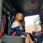 A young boy wearing a hooded sweatshirt sits in a fire truck and smiles. Other boys are also in their seats smiling.