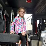 A girl wearing a multi-colored shirt and glasses smiles from inside the fire truck.