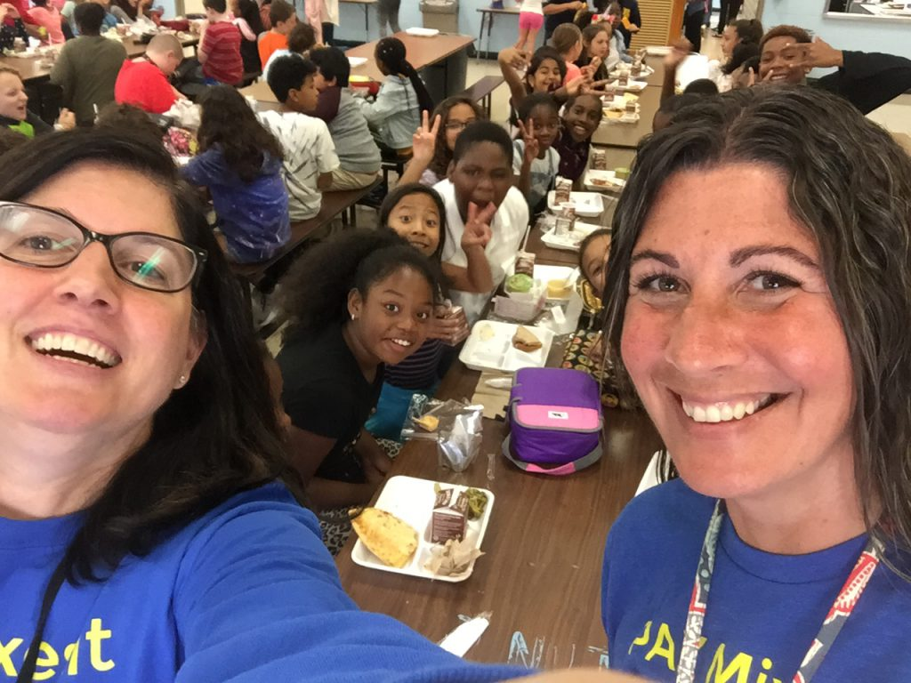Two teachers stand in front of a long table filled with elementary students eating their lunch