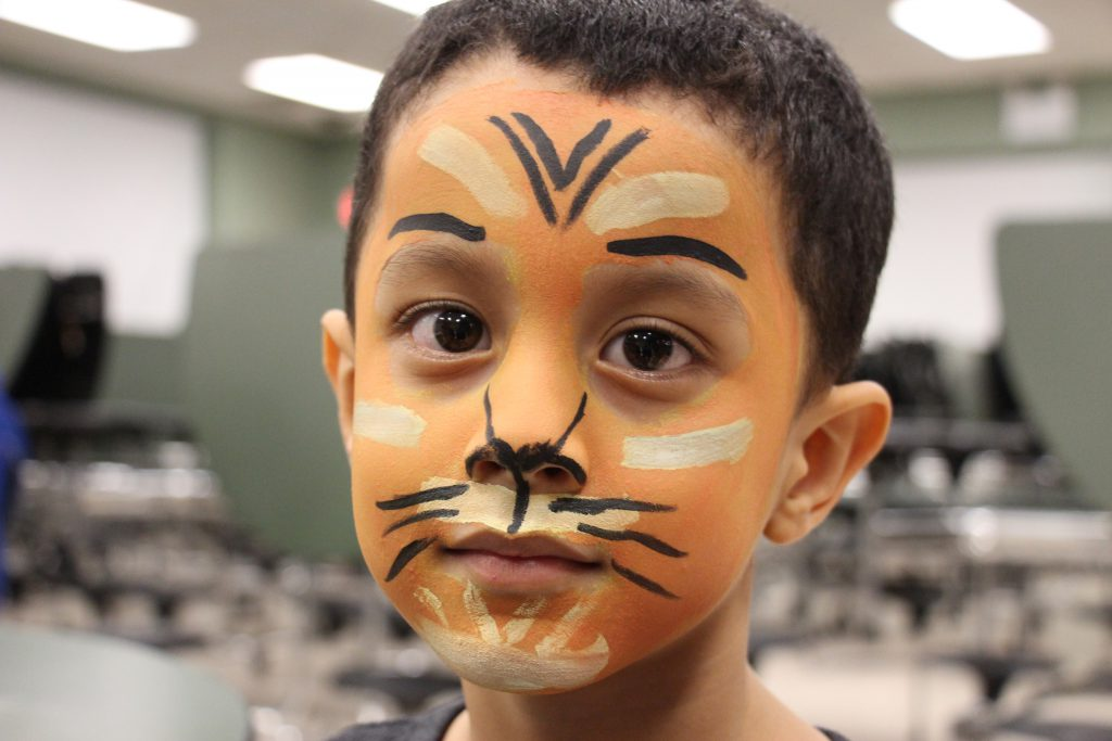 A young boy with his face painted as a tiger.