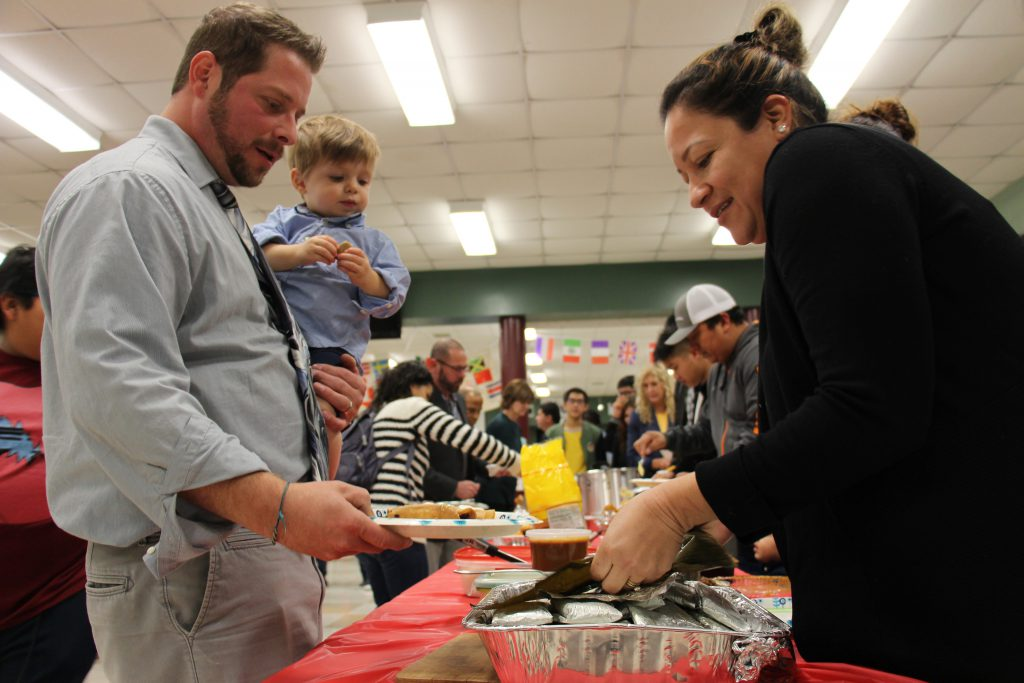 A man holding a toddler holds out his plate as a woman puts food on it. Behind them are lines of people getting food.