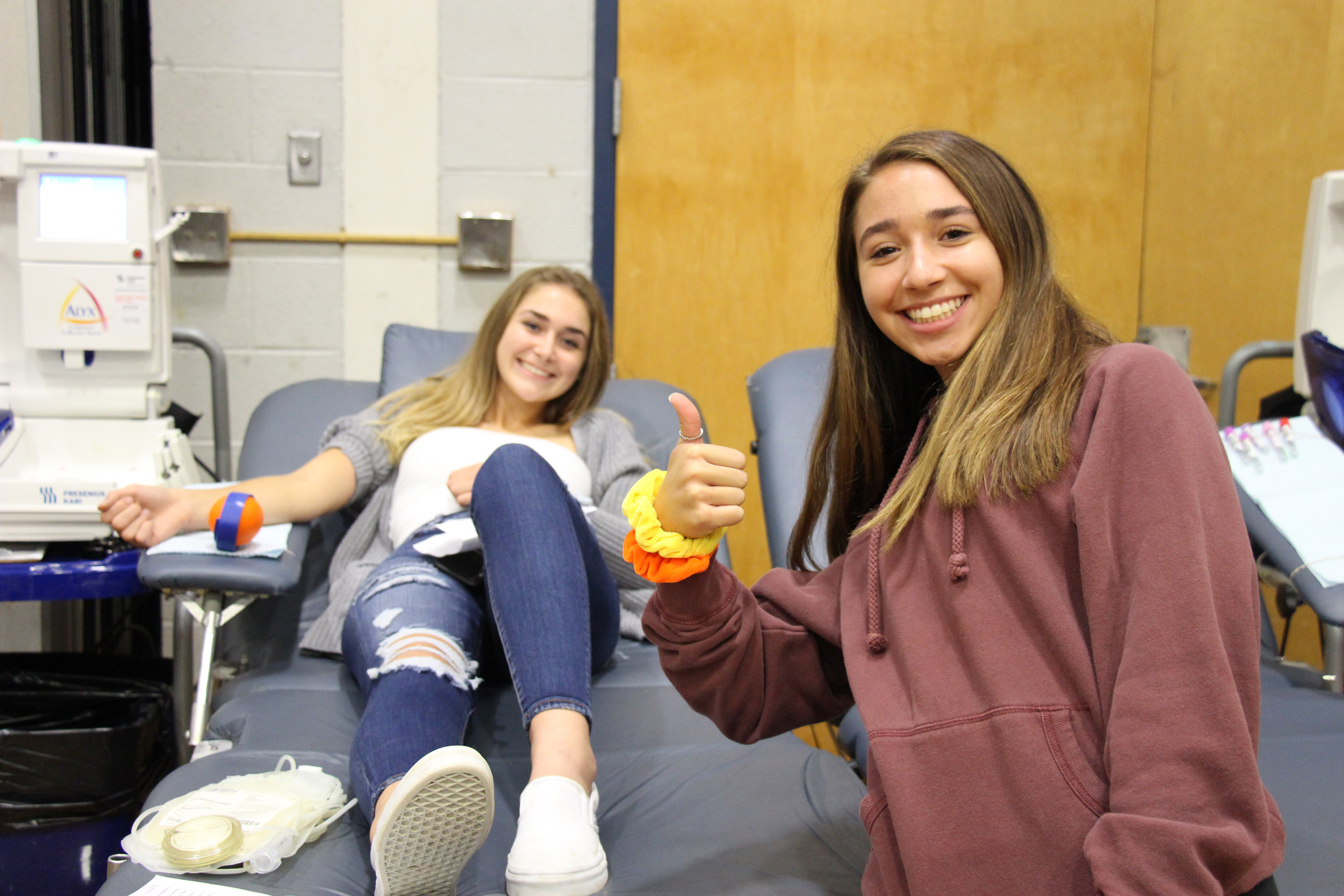 Two young women - one on a gurney giving blood and another in front of her giving a thumbs up.