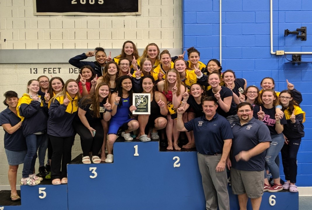 A large group of girls and their coaches are on the podium which has spaces labeled 1, 2 and 3.