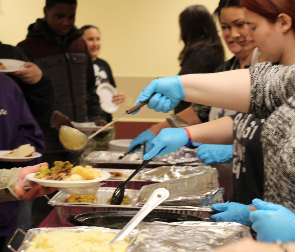 volunteers wearing blue gloves ladle out Thanksgiving food onto plates