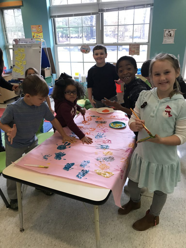 A group of six elementary school children stand around a table that has a large piece of paper on it. The are putting their handprints in paint on it.