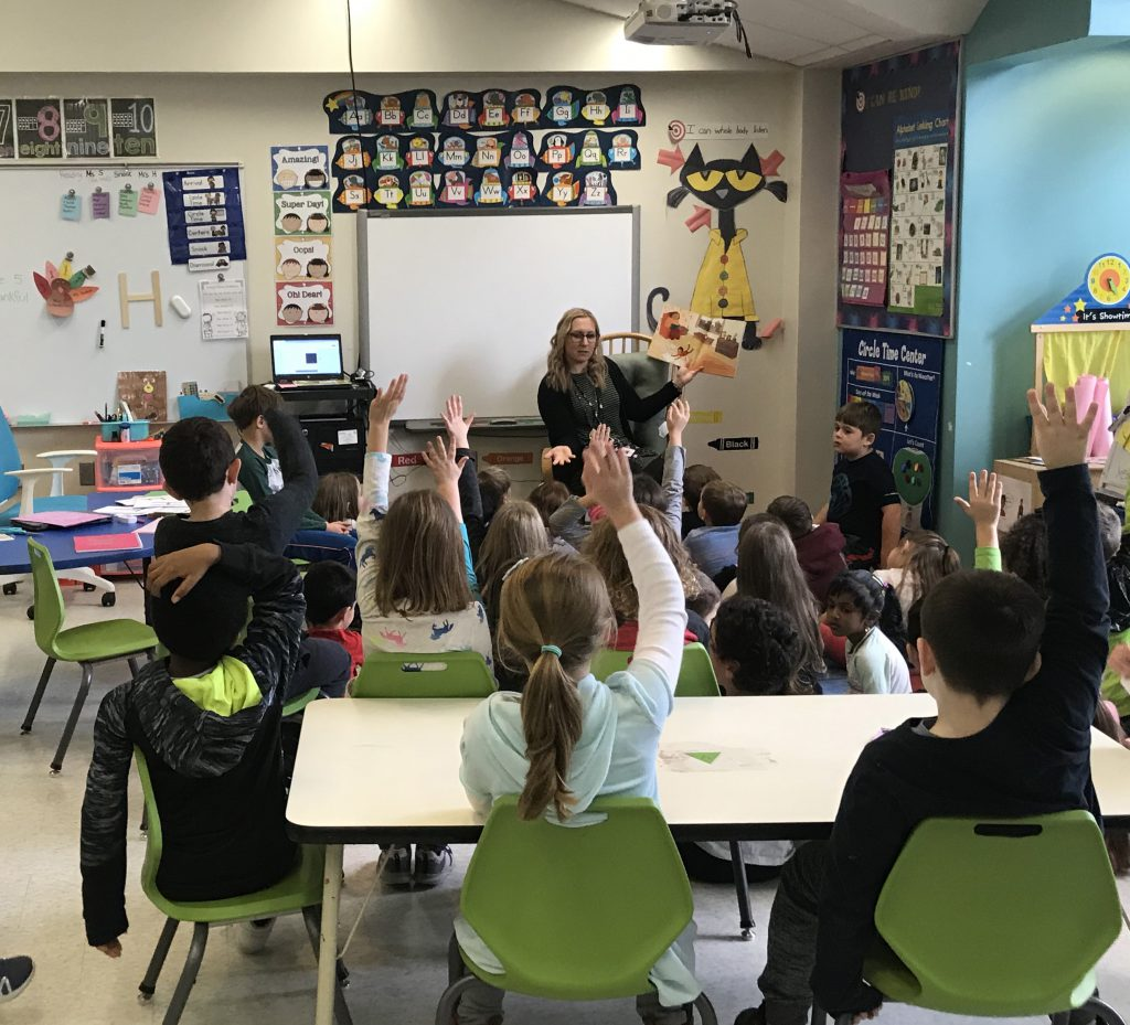 A teacher sits at the front of a class reading from a book, holding it up so the students can see it. The students are sitting on the run as well as in chairs, many with their hands up.