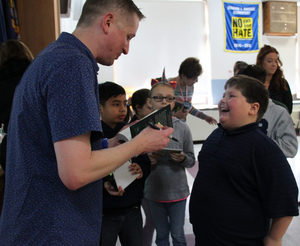 A boy smiles broadly as the man in the blue shirt signs a copy of a book