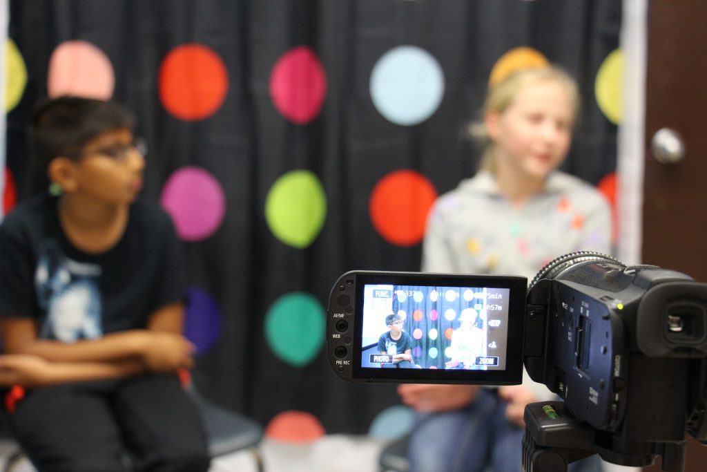 Two students in front of a multi-colored polka dot background. They are seen through the video screen of a camera.