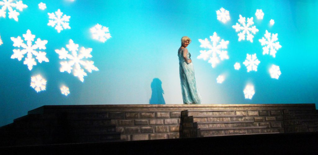 Against a blue backdrop with large snowflakes reflected on it, a young woman dressed in a blue dress stands on a wall.